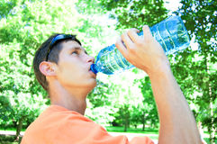 Thirst. Young man drinking water in heat Stock Image