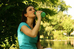 Thirst. A young woman drinking from a green bottle, quenching her thirst Stock Images