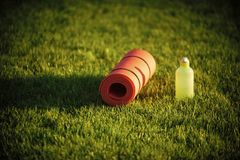 Thirst, dehydration, drinking water. Mat and plastic bottle on green grass, gym equipment. Health, diet, energy. Sport, yoga, fitness, pilates gym equipment royalty free stock image