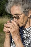 Thirst of old woman Stock Image