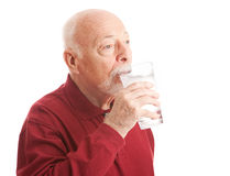 Thirst Quenching Filtered Water. Senior man quenches his thirst with a big glass of filtered ice water. White Background royalty free stock image