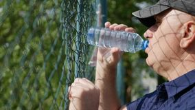 Thirsted Person Back of a Metallic Fence Drinking Water stock image