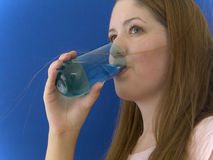 Thirsty 3. Woman drinking water out of a colored glass, looking up royalty free stock photo