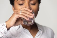 Free Thirsty African American Girl Drinking Clean Mineral Water Close Up Stock Photography - 162057542