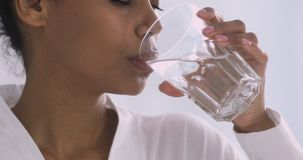 Thirsty african woman holding glass drinking water in morning, closeup