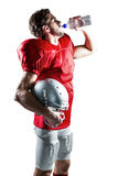 Thirsty American football player in red jersey drinking water. Thirsty American football player in red jersey holding helmet while drinking water on white Royalty Free Stock Images