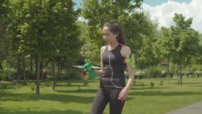 Sporty woman in headphones drinking during running stock video footage