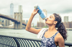 Thirsty athlete drinking after long run in New york city. Brooklyn bridge and skyline in the background stock photography