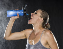 Thirsty Athletic Woman Drinking Water in a Bottle Stock Photo