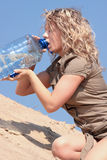 Thirsty blond woman on desert Royalty Free Stock Photo