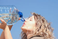 Thirsty blond woman on desert Stock Photo