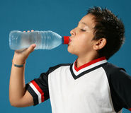 Thirsty boy drinking water. Thirsty boy drinking fresh water wearing sport clothes Stock Image