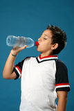 Thirsty boy drinking water. Thirsty boy drinking fresh water wearing sport clothes Stock Photography