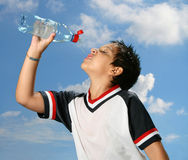 Thirsty boy drinking water out. Thirsty boy drinking fresh water outdoors wearing sport clothes royalty free stock image