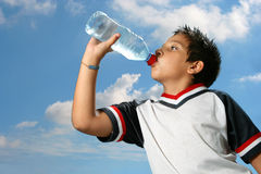 Thirsty boy drinking water out. Thirsty boy drinking fresh water outdoors wearing sport clothes stock image