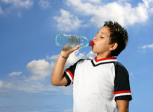 Thirsty boy drinking water out. Thirsty boy drinking fresh water outdoors wearing sport clothes stock photos