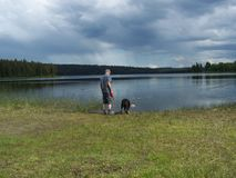 Man and dog walking by lake. With dark storm clouds in background stock images