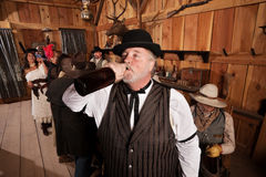 Thirsty Drunkard in Saloon. Overweight men drinks from a bottle of alcohol in a saloon Royalty Free Stock Photo