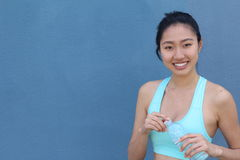 Thirsty fitness Asian girl holding bottle of water with copy space.  Royalty Free Stock Photo