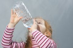 Thirsty girl. Girl with bottle of fresh water Royalty Free Stock Images