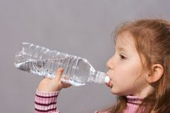 Thirsty girl drinking clean. Girl with bottle of fresh water Royalty Free Stock Photos