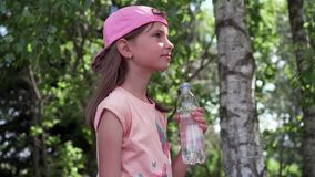 Thirsty girl drinking water in a park stock footage