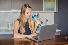 Thirsty girl drinks water, uses laptop computer for blogging in networks, watches film, connected to wireless internet. Woman reads news on web site stock image