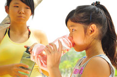 Thirsty girls drinking from their bottle Royalty Free Stock Images