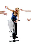 Thirsty gym colleagues. Girl water pours from the boottle during training on stationary bicycle in gym - isolated on white background Stock Photos