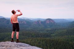 Thirsty hiker in black pants with bottle of water. Sweaty tired tourist on the peak of sandstone rocky park Saxony Switzerland wat stock images