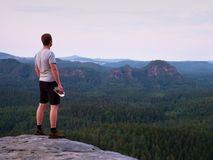 Thirsty hiker in black pants with bottle of water. Sweaty tired tourist on the peak of sandstone rocky park Saxony Switzerland wat Royalty Free Stock Photo