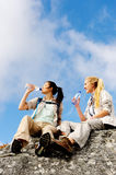 Thirsty hikers. Two women take a break from trekking and rest on a rock outdoors while drinking water royalty free stock images