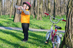 Thirsty little boy drinking bottled. Thirsty little boy out riding his bicycle along a path through rural woodland stopping to drink bottled water Royalty Free Stock Images