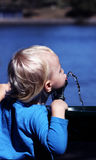 Thirsty little boy drinking water. Cute young blond boy drinking water out of a drinking fountain Stock Image