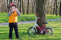 Thirsty little boy drinking water. From plastic bottle while out riding in rural woodland on his bicycle which  propped against  tree Stock Photos