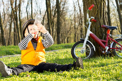 Thirsty little boy out riding having a drink. Thirsty little boy out riding on his bicycle sitting on the lush green grass of a wooded park having a drink of Royalty Free Stock Photography