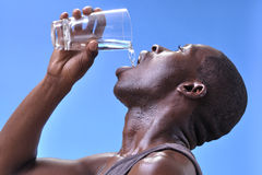 Thirsty man. Closeup of thirsty sweaty young athletic black man pouring clean pure water into mouth from glass on blue sky background Stock Photo