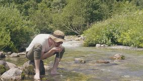 Thirsty man drinking spring water from hand while hiking mountain stock video