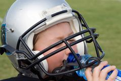 Thirsty Player. Young boy getting a drink during a football game stock photo