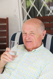Thirsty senior man drinking water Stock Images