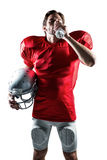 Thirsty sportsman in red jersey holding helmet while drinking water Royalty Free Stock Photography