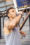 Thirsty sportsman take a rest and drinking water after running. Stock Image