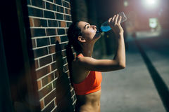 Thirsty sportswoman drinking water Stock Photo