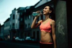 Thirsty sportswoman drinking water Stock Photos