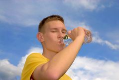 Thirsty teenager. Drinks water on sunny day after playing basketball Royalty Free Stock Photography