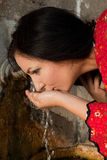 Thirsty at a well. Young woman in bulgarian national dress drinking at an old well in the village of yeravna Royalty Free Stock Photo