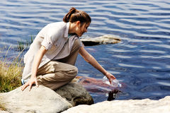 Thirsty woman. Hiking woman fills up her water bottle in a fresh water lake stock photography