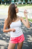 Thirsty woman drink water from bottle on stadium. Drinking water after training and workout. Thirst and dehydration. Refreshment a Stock Photography