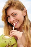 Thirsty woman drinking coconut water on the beach Royalty Free Stock Images