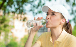 Thirsty woman drinking fresh water Stock Images